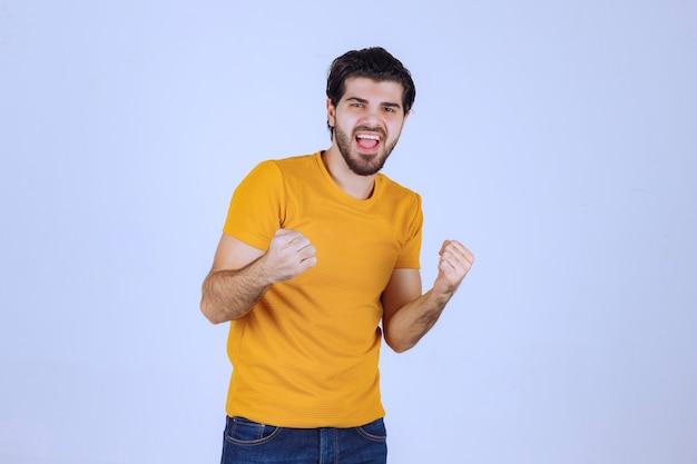 Mann mit bart, der seine faust- und armmuskulatur demonstriert und sich mächtig fühlt
