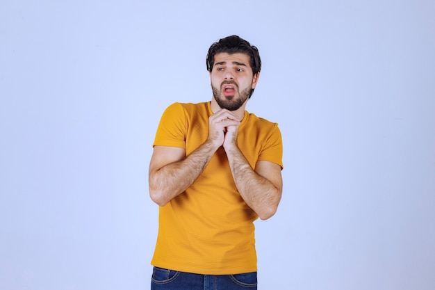 Mann mit bart, der seine hände vereint und betet und um etwas bittet