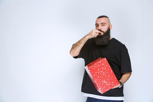 Mann mit bart, der seine rote geschenkbox hält, sie genießt und sich glücklich fühlt.