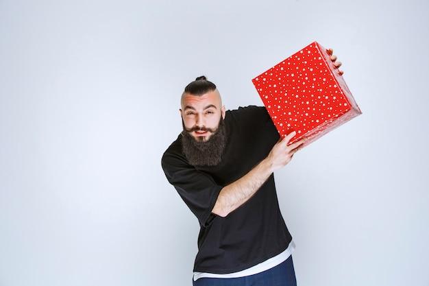 Mann mit bart, der seine rote geschenkbox zeigt.
