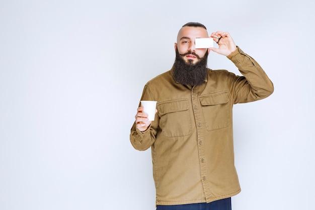 Mann mit bart, der seine visitenkarte zeigt, während er eine tasse kaffee hält.
