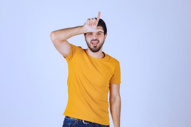Mann mit bart, der verliererhandzeichen zeigt.