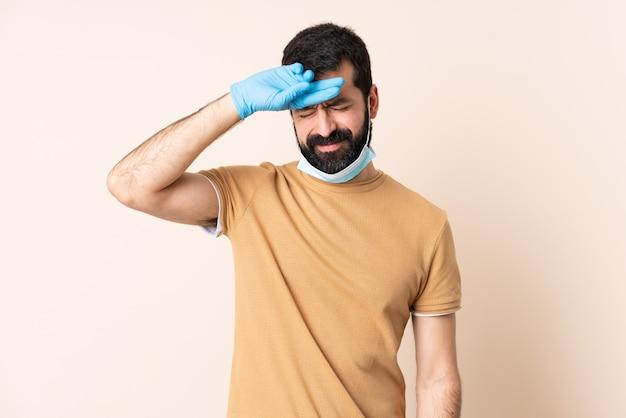 Mann mit bart, der vor dem coronavirus mit einer maske und handschuhen über isolierter wand mit müdem und krankem ausdruck schützt