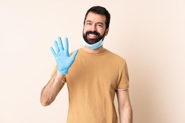 Mann mit bart, der vor dem coronavirus mit einer maske und handschuhen über isolierter wand schützt, die fünf mit den fingern zählt