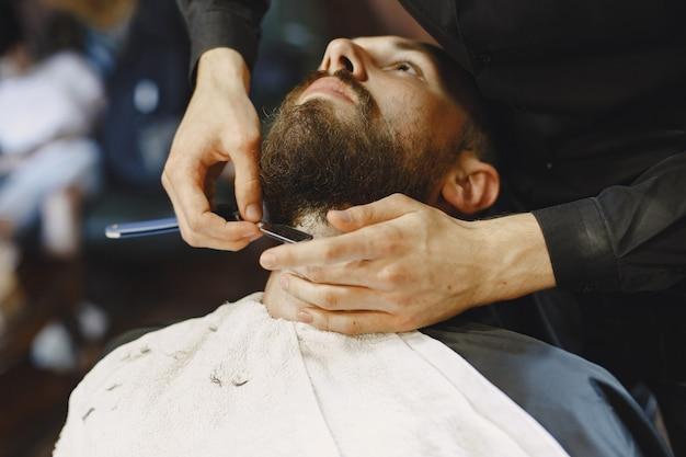 Mann mit bart. friseur mit einem kunden. mann mit einer rasur.