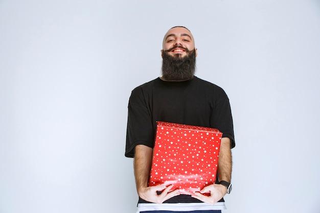 Mann mit bart hält eine rote geschenkbox