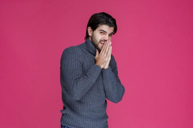 Mann mit bart hält seine hände so, als würde er beten oder etwas wünschen.