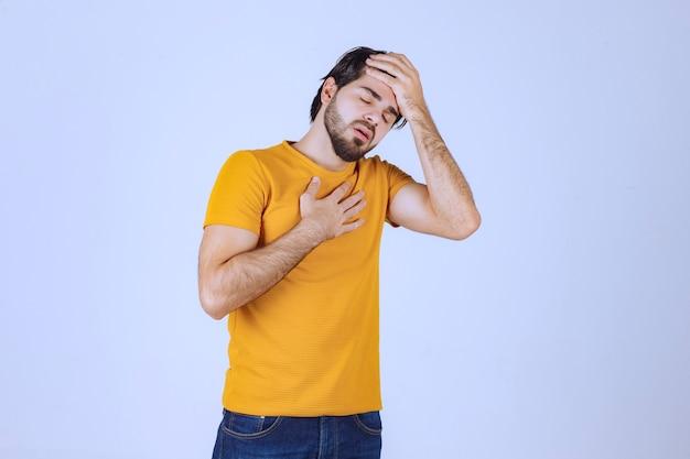 Mann mit bart hat kopfschmerzen und fühlt sich krank