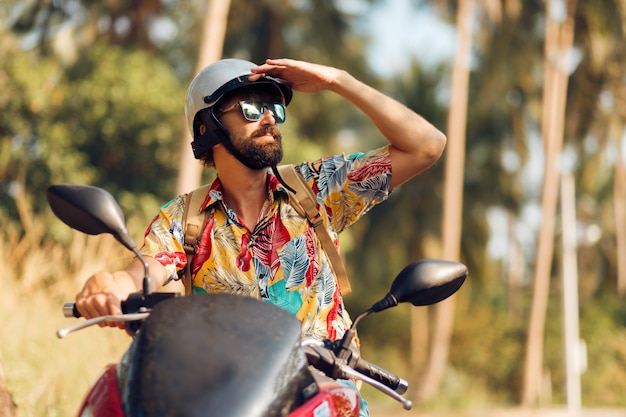 Mann mit bart im bunten tropischen hemd, das auf motorrad sitzt