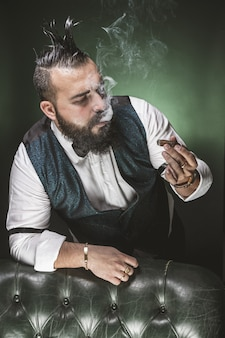 Mann mit bart, in anzug und fliege gekleidet, beim rauchen eine zigarre betrachtend.