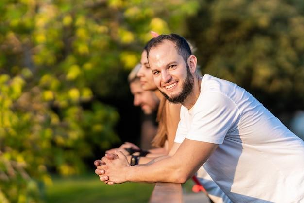 Mann mit bart lächelt in die kamera, während er sich mit seinen freunden auf einem geländer ausruht