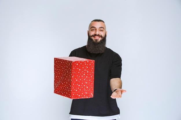 Mann mit bart mit roter geschenkbox