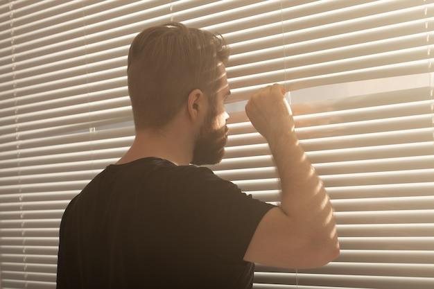 Mann mit bart späht durch loch in den jalousien