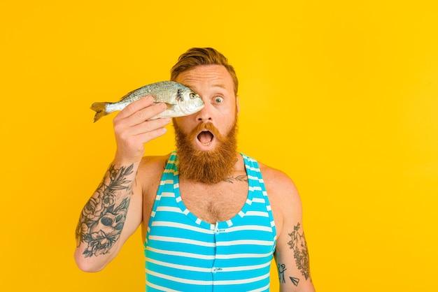Mann mit bart, tattoos und badeanzug hat einen fisch gefangen