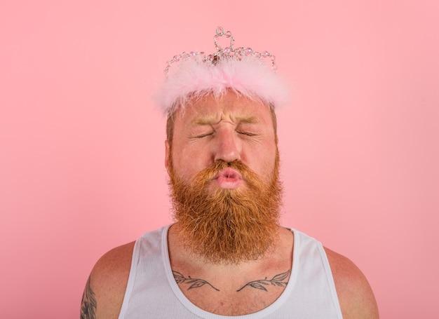 Mann mit bart, tattoos und krone benimmt sich wie eine prinzessin