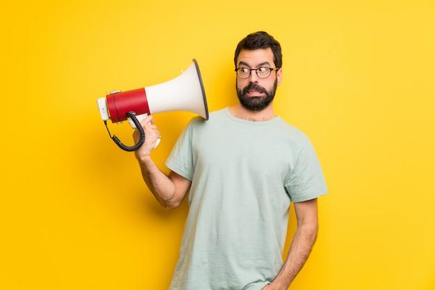 Mann mit bart und grünem hemd, das ein megaphon nimmt, das viele geräusche macht