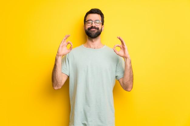 Mann mit bart und grünem hemd in der zenhaltung