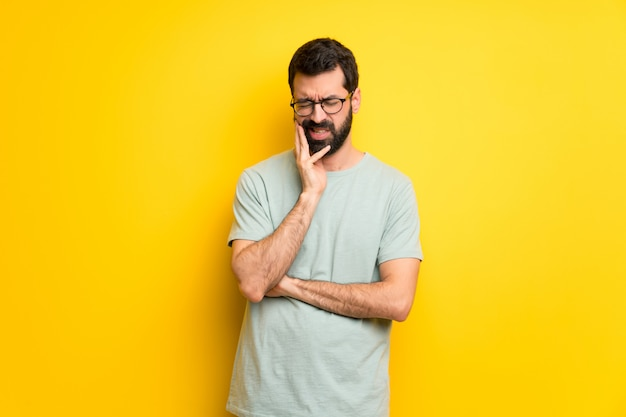 Mann mit bart und grünem hemd mit zahnschmerzen
