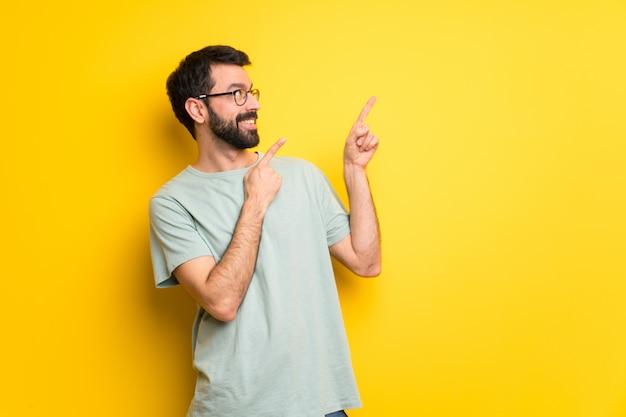 Mann mit bart und grünem hemd zeigend mit dem zeigefinger und oben schauen