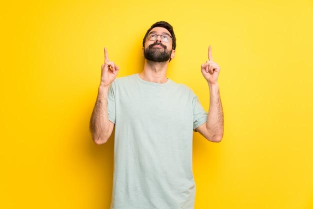 Mann mit bart und grünem hemd zeigt mit dem zeigefinger eine großartige idee