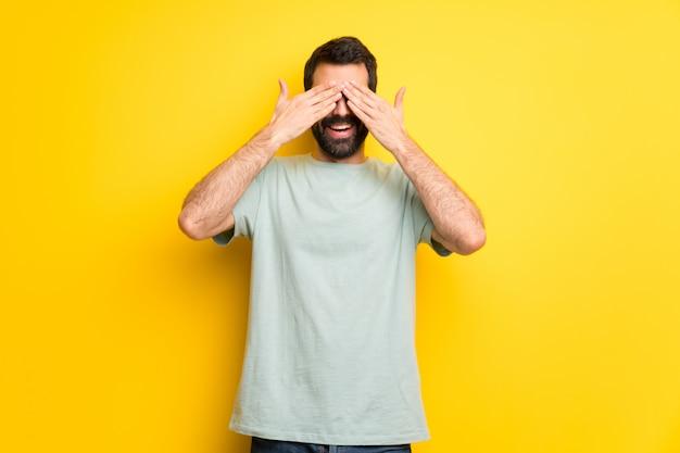 Mann mit bart und grünen hemdbedeckungsaugen durch hände. überrascht zu sehen, was vor uns liegt