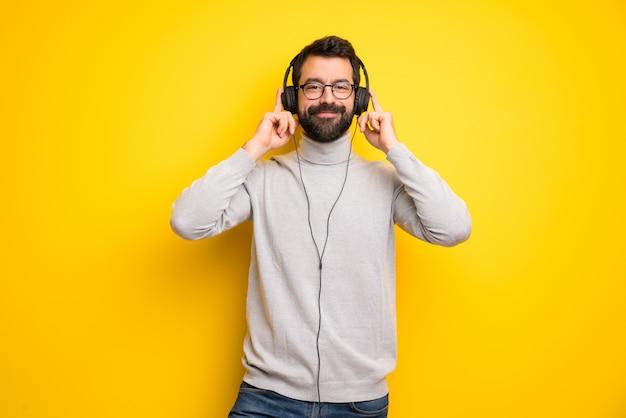 Mann mit bart und rollkragen hört musik mit kopfhörern