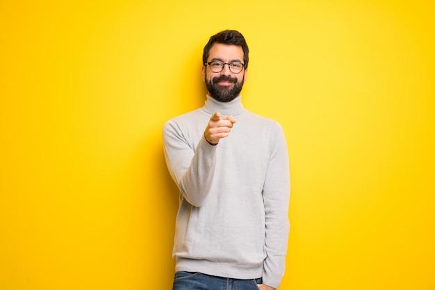 Mann mit bart und rollkragen zeigt mit einem selbstbewussten ausdruck auf sie
