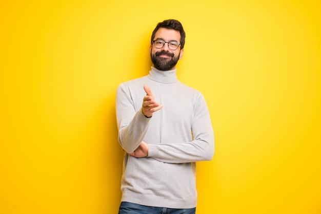 Mann mit bart und rollkragenpullover beim händeschütteln