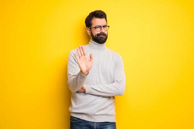 Mann mit bart und rollkragenpullover machen stop-geste und leugnet eine situation, die falsch denkt