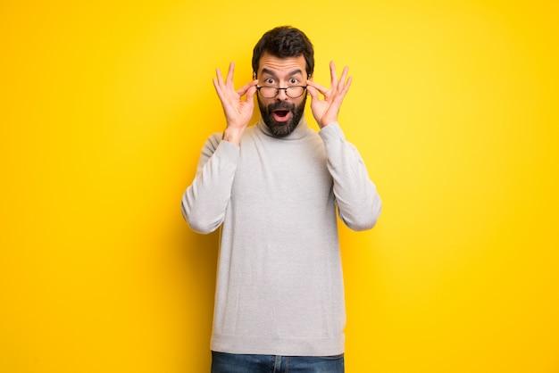 Mann mit bart und rollkragenpullover mit brille und überrascht