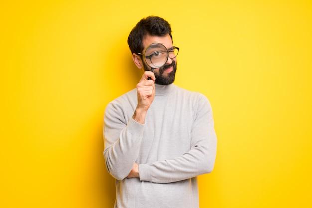 Mann mit bart und rollkragenpullover nimmt eine lupe und schaut durch sie hindurch