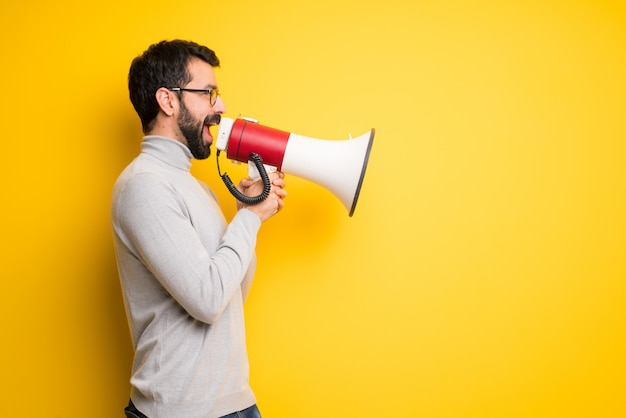 Mann mit bart und rollkragenpullover schreit durch ein megaphon, um etwas in seitlicher position anzukündigen