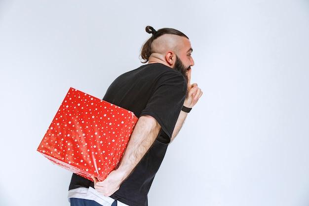 Mann mit bart versteckt eine rote geschenkbox hinter sich.