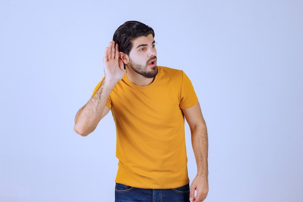 Mann mit bart zeigt sein gehör und versucht aufmerksam zuzuhören