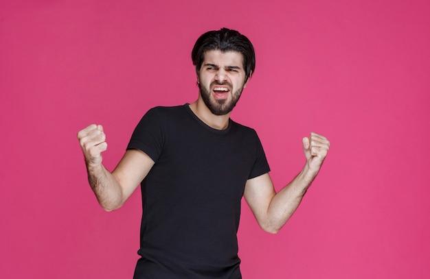Mann mit bart zeigt seine fäuste und fühlt sich mächtig