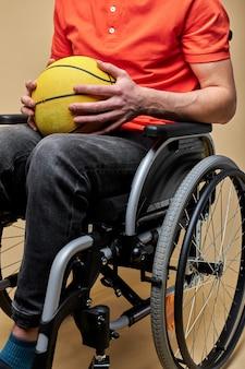 Mann mit basketballball sitzt auf rollstuhl gegen farbwand, sport für behinderte menschen. nahaufnahmefoto