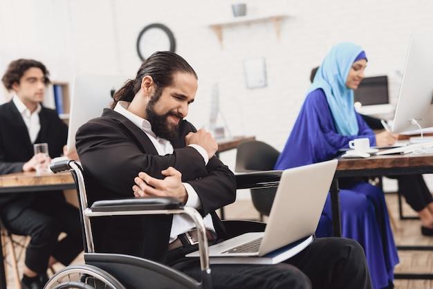 Mann mit behinderung fühlt schmerzarbeiter mit laptop.