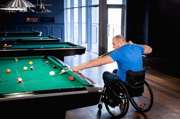 Mann mit behinderungen im rollstuhl spielen billard im club