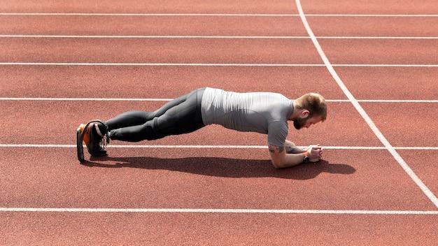 Mann mit beinprothese, der plank full shot macht