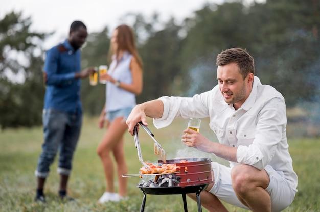 Mann mit bier beim grillen für freunde