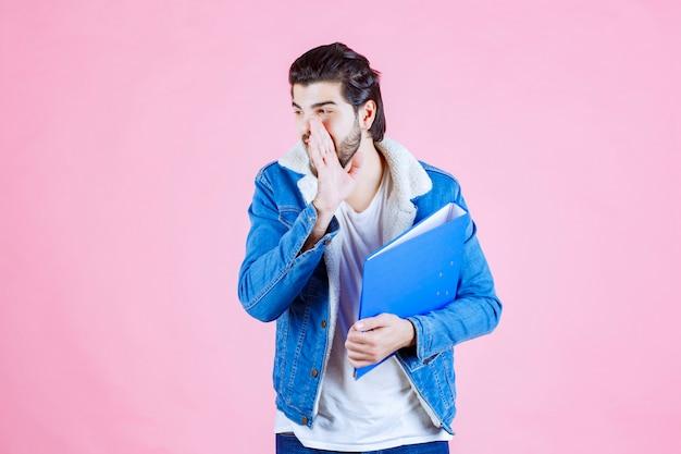 Mann mit blauem ordner, der flüstert und klatscht