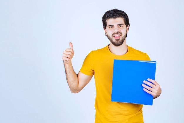 Mann mit blauem ordner, der freundliche und friedliche posen gibt.