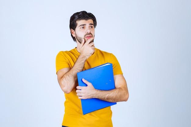 Mann mit blauem ordner sieht verwirrt oder unerfahren aus.