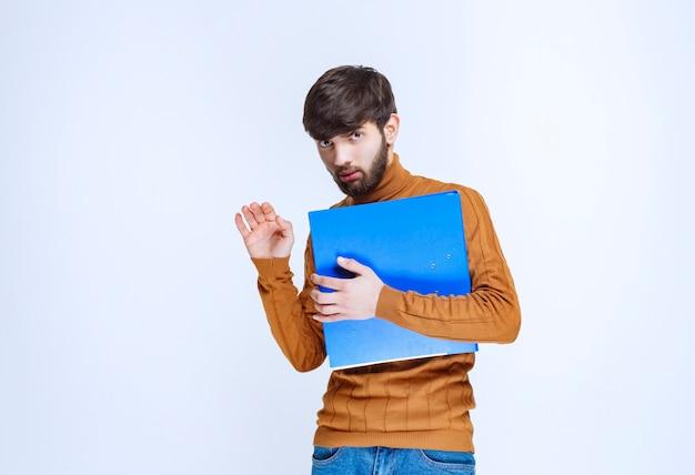 Mann mit blauem ordner sieht verwirrt und verängstigt aus.