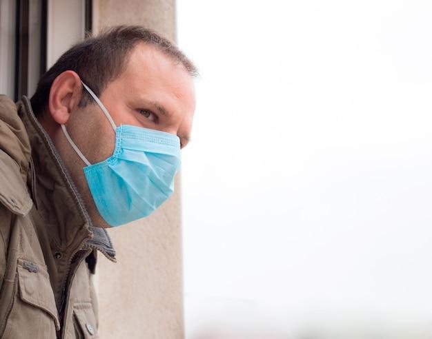 Mann mit blauer einweggesichtsmaske im freien, die sich umschaut