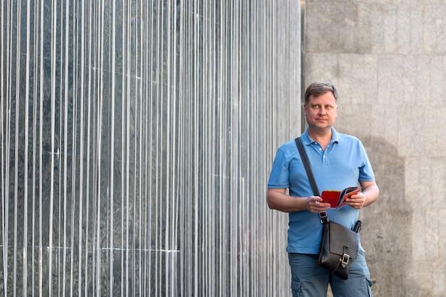 Mann mit blauer kleidung hält werbeartikel in seinen händen