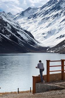 Mann mit blick auf den see laguna del inca, umgeben von bergen in chile