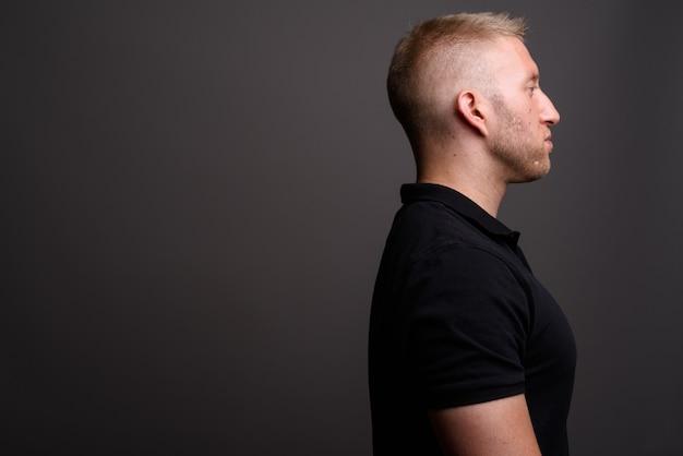 Mann mit blondem haar, das schwarzes poloshirt auf grauer wand trägt