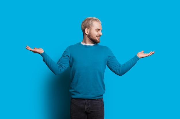 Mann mit blonden haaren und bart zeigt eine balance mit seinen händen, die fröhlich auf eine blaue wand schauen und lächeln