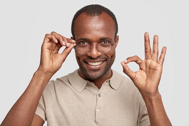 Mann mit borsten und dunkler haut zeigt ein gutes zeichen, hat einen positiven ausdruck, trägt eine brille und hält die hand am rand